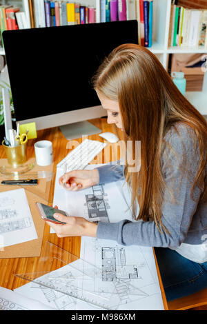Young woman working in architecture office, using phone - Stock Photo