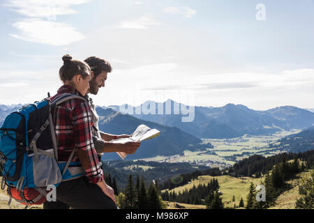 Austria, Tyrol, young couple looking at map in mountainscape - Stock Photo