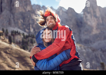 Happy young couple hugging in windy mountains - Stock Photo