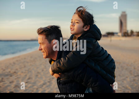 Father carrying son piggyback on the beach - Stock Photo