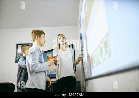 Teacher with students in class at interactive whiteboard - Stock Photo