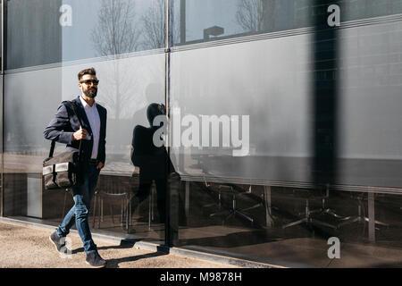 Businessman wearing sunglasses walking along building - Stock Photo