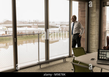 Serious mature businessman standing at the window looking out - Stock Photo