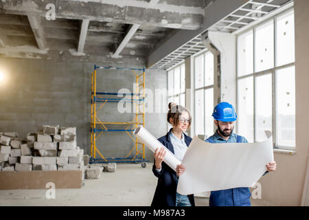Builder with businesswoman at the construction site - Stock Photo
