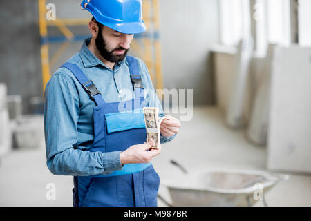 Builder with salary at the construction site - Stock Photo