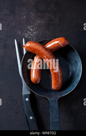 Two minced pork sausage in pan and a meat fork on rusty metal - Stock Photo