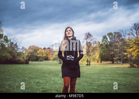 Portrait of young woman with camera walking on a meadow in autumnal park - Stock Photo