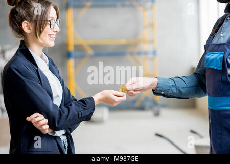 Woman giving cryptocurrency to a builder - Stock Photo