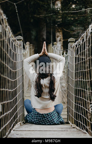 Young woman in yoga pose sitting on a suspension bridge - Stock Photo