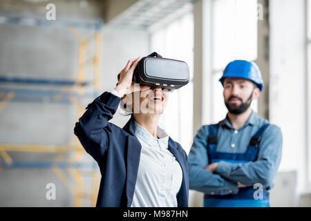 Woman client wearing VR glasses at the construction site - Stock Photo