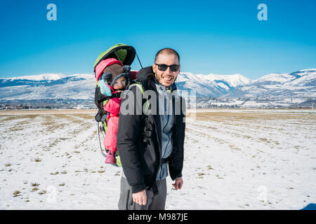 Spain, Puigcerda, father with baby girl in a kid carrier backpack during a hike at winter - Stock Photo