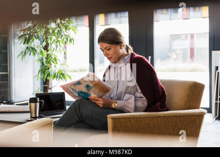 Young woman sitting in armchair reading documents - Stock Photo