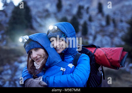 Two happy young women wearing headlamps embracing in the mountains - Stock Photo