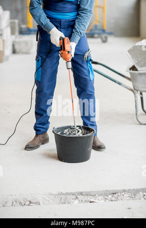 Builder mixing plaster at the construction site - Stock Photo