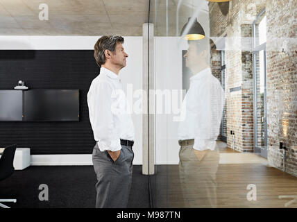 Mature businessman reflecting in glass pane of modern conference room - Stock Photo