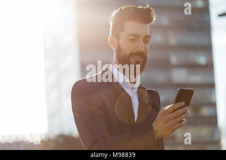 Businessman using cell phone outside office building - Stock Photo