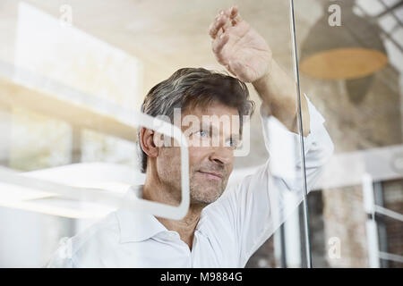 Portrait of mature businessman leaning against glass wall in office - Stock Photo