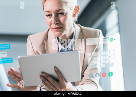 Businesswoman sitting in office, using digital tablet - Stock Photo