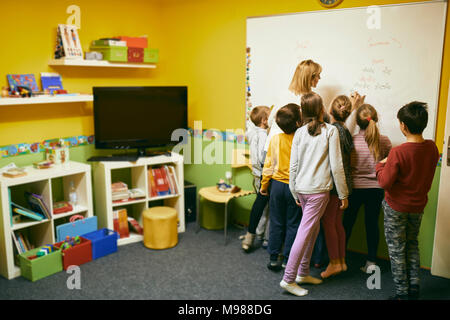 Teacher with students writing on whiteboard - Stock Photo