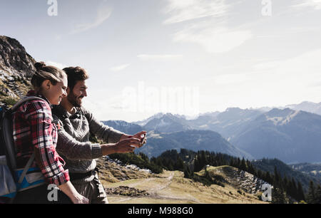 Austria, Tyrol, smiling young couple taking a selfie in mountainscape - Stock Photo