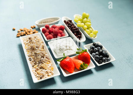 ingredients for muesli, chia seeds, curd, cranberries, grapes, blueberries, raspberries, strawberry, almonds - Stock Photo