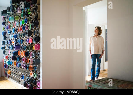 Mature woman standing in a room with assortment of yoga mats - Stock Photo