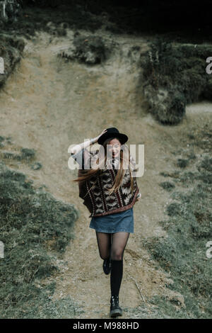 Fashionable young woman wearing hat and poncho running downhill - Stock Photo