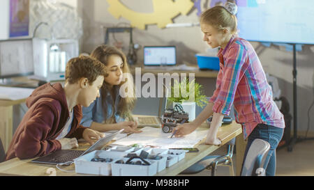 In a Computer Science Class Teacher Explains Programming for Children Showing it on Interactive Whiteboard. Stock Photo