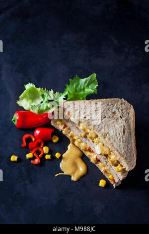 Chicken sandwich with corn, pepperoni and curry sauce on dark ground - Stock Photo