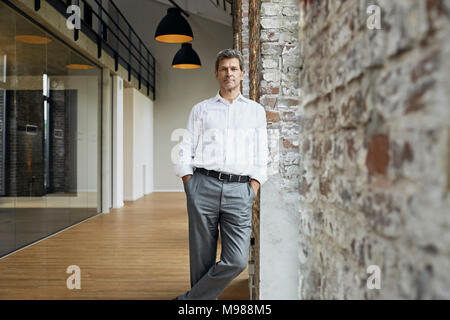Portrait of confident businessman leaning against brick wall in modern office - Stock Photo