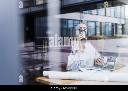 Young woman with laptop, cell phone and documents drinking coffee behind windowpane - Stock Photo