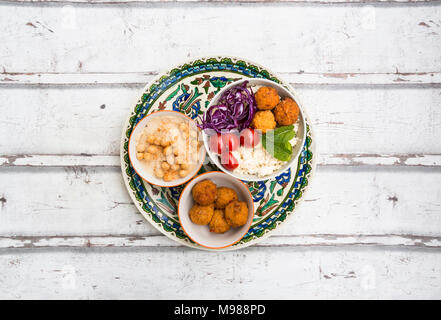 Sweet potato balls, Couscous, Hummus and vegetables in bowls - Stock Photo