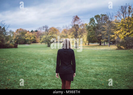 Back view of young woman walking on a meadow in autumnal park - Stock Photo
