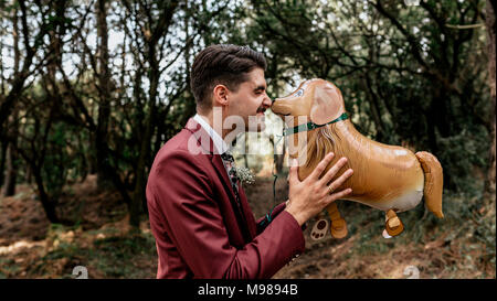 Man wearing suit in forest playing with funny dog-shaped balloon - Stock Photo