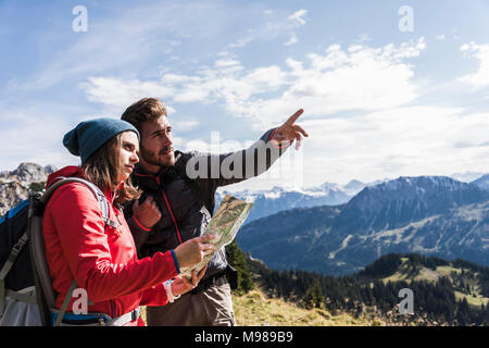 Austria, Tyrol, young couple with map in mountainscape looking around - Stock Photo