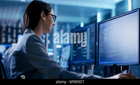 Close-up Shot of Female IT Engineer Working in Monitoring Room. She Works with Multiple Displays. - Stock Photo