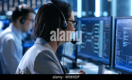 In the System Control Center Woman working in a Technical Support Team Gives Instructions with the Help of the Headsets. Possible Air Traffic - Stock Photo