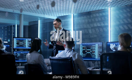 Supervisor Holds Briefing for His Employees in System Control Center Full of Monitors and Servers. Possibly Government Agency Conducts Investigation. - Stock Photo