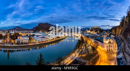 Austria, Salzburg State, Salzburg, panoramic view of Salzach river, old town and castle Hohensalzburg in the evening - Stock Photo