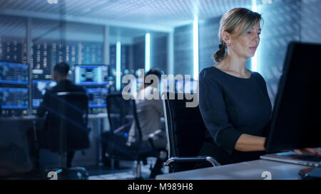 Female IT Engineer Works on Her Desktop Computer in Government Surveillance Agency. In the Background People at Their Workstations with Screens - Stock Photo