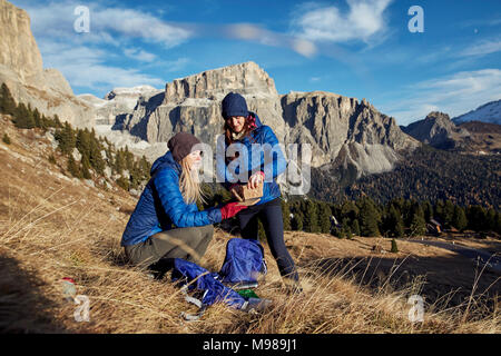 Two young women hiking in the mountains having a break - Stock Photo
