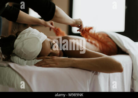 Young woman receiving a massage with feathers in a spa - Stock Photo