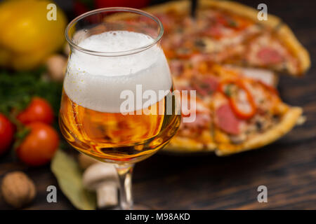 Glass of beer and appetizing pizza with salami, ham, mushrooms and vegetables on wooden stand in the form of hemp near tomatoes, mushroom and pepper o - Stock Photo
