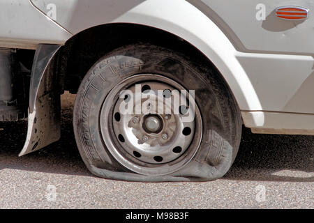 Aqaba, Jordan, March 7, 2018: Flat tire on the front wheel of a van on a bad road in Aqaba, middle east - Stock Photo