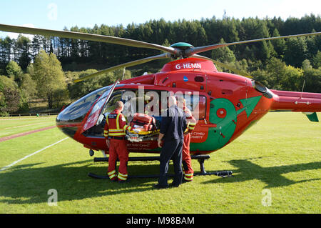 Crew members standing outside an Airbus helicopter of the Wales Air Ambulance service - Stock Photo