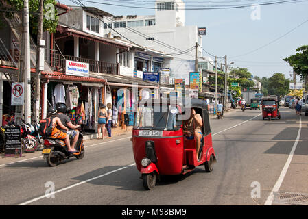 The main tourist area street road in Hikkaduwa, Sri Lanka on a sunny day with blue sky, tuk tuks and scooters. - Stock Photo