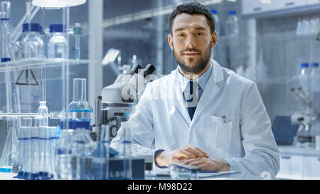 Young Male Research Looks into Camera and Smiles. He's Sitting in a High-End Modern Laboratory with Beakers, Glassware, Microscope and Working Monitor - Stock Photo