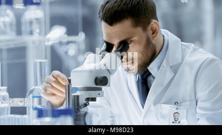 Close-up Shot of Research Scientist Adjusts His Microscope. He's Working in a High-End Modern Laboratory with Beakers, Glassware, Microscope, Monitors - Stock Photo