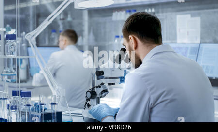 Shot of Research Scientist Adjusts His Microscope. He's Working in a High-End Modern Laboratory with Beakers, Glassware, Microscope and Monitors - Stock Photo