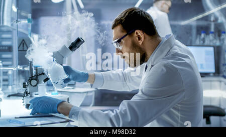 In a Chemical Research Laboratory Scientist Mixes Smoking Compounds in Beakers. - Stock Photo